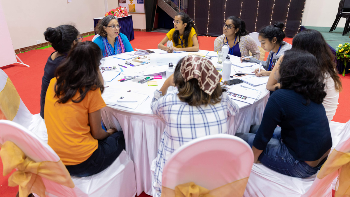 MHC Shakti speaker and participants interacting in a small group setting