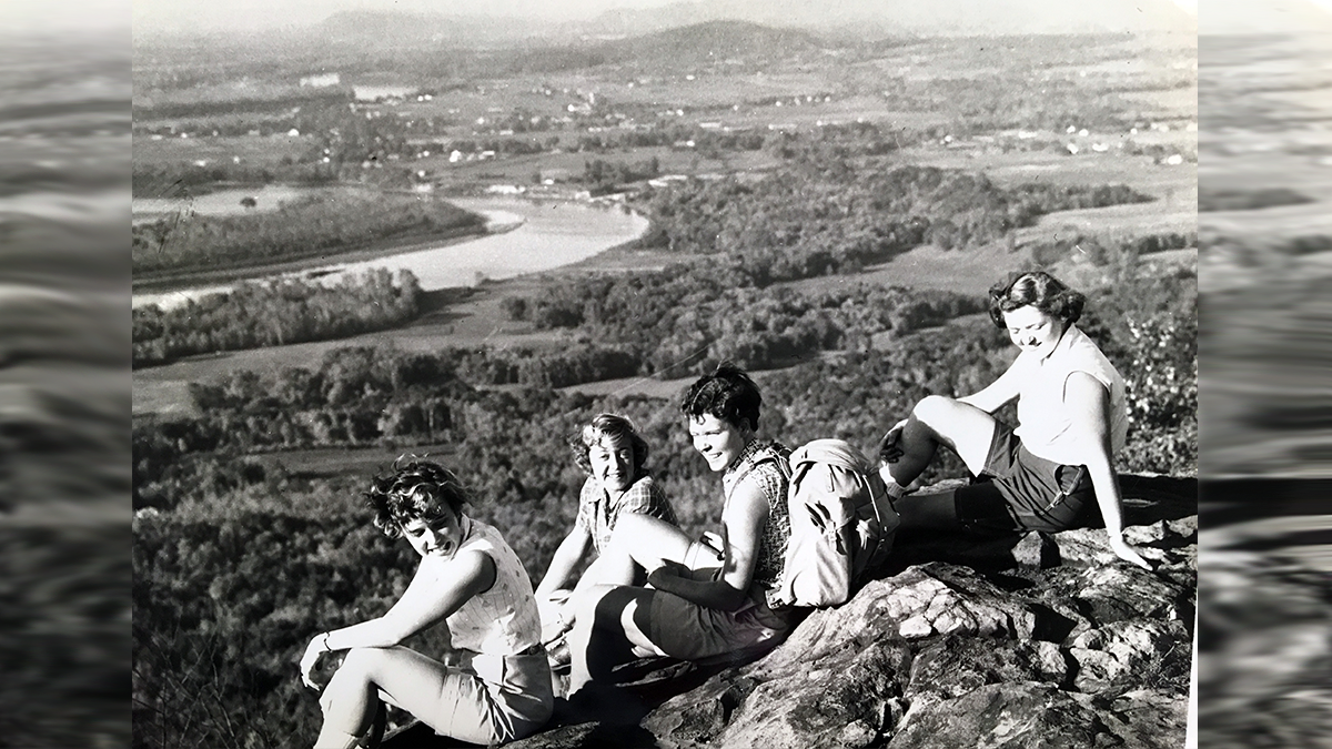 Four students enjoying the view of the Connecicut River from atop Mount Holyoke on Mountain Day 1955