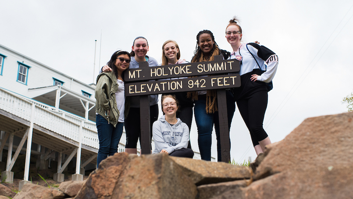 """A group of students by the summit sign that says """"Mt. Holyoke Summit. Elevation 942 feet"""""""