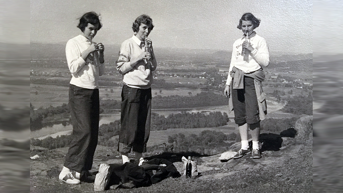 Three students drinking soda at the top of Mount Holyoke on Mountain Day 1940