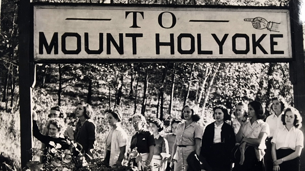 """A group of students standing underneath a sign marking """"To Mount Holyoke"""" on Montain Day 1946"""