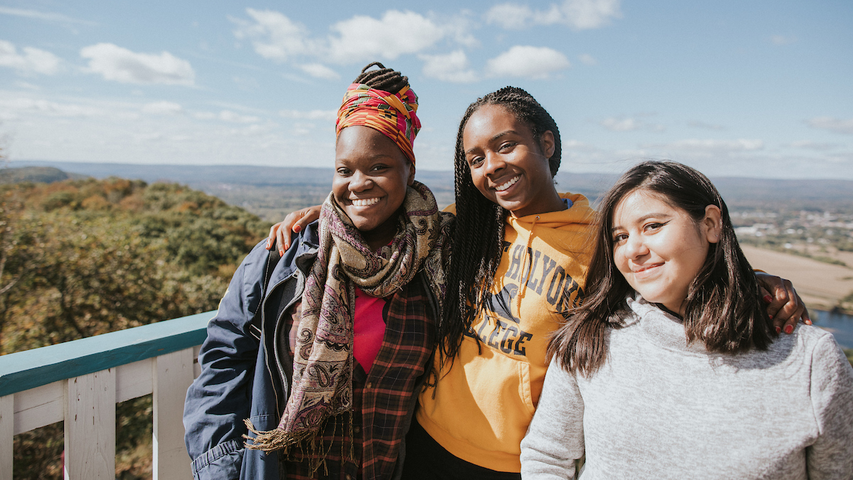 Three students on the deck of the Summit House atop Mount Holyoke on Mountain Day 2018