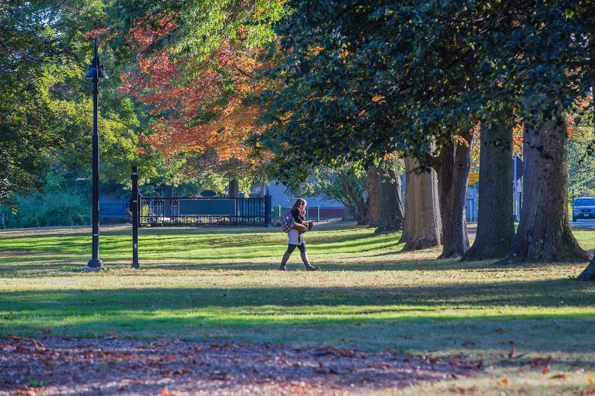 Photo of a student walking on campus in the fall