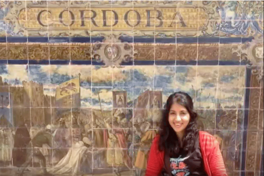 Photo of a student standing in front of a mural in Cordoba