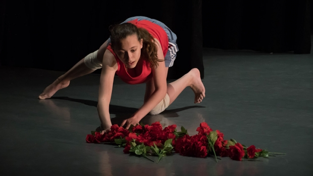 A single dancer on a darkened stage, crouching, reaching toward a pile of roses on the floor.