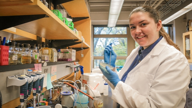 Megan Littlehale '19 stands by a lab bench at Mount Holyoke, holding a pipette and a petri dish.