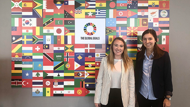 Christine Skroski '20, standing with her mentor in front of a wall of flags.