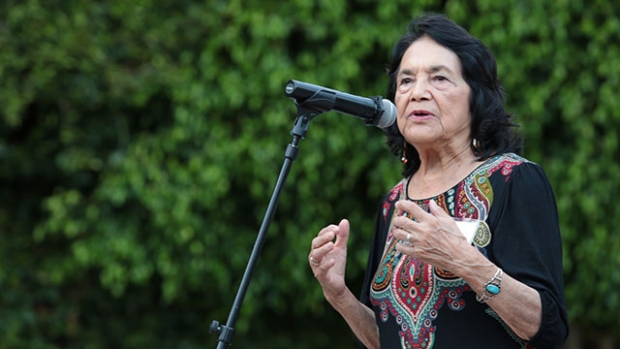 This is a photograph of Dolores Huerta addressing a crowd in front of a microphone.