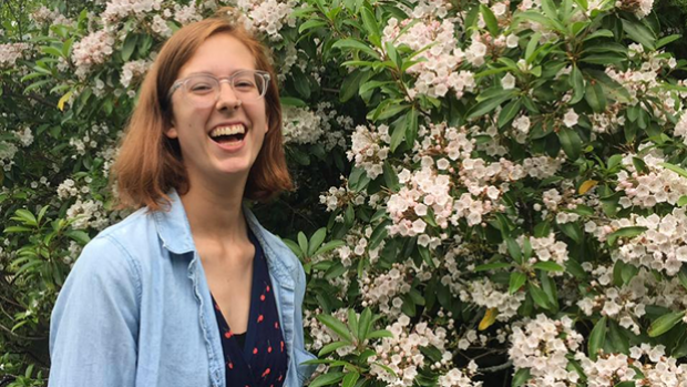 Lydia Henning, laughing in front of a bush with pink flowers.