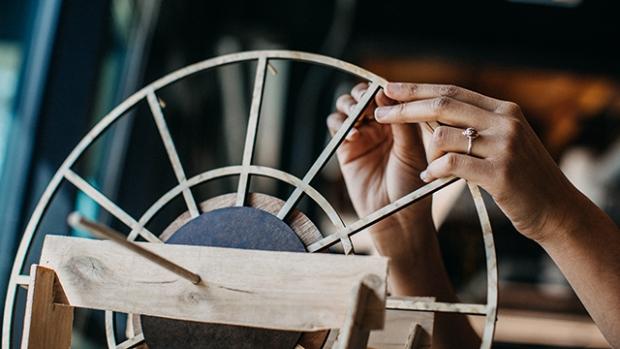 This is a photograph of a pair of hands working on a spoked wooden circle in the Fimbel Lab.