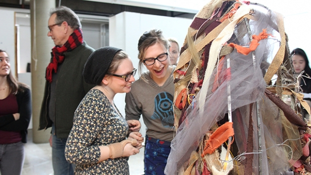"Students discuss an art project during the ""X-Section"" opening."