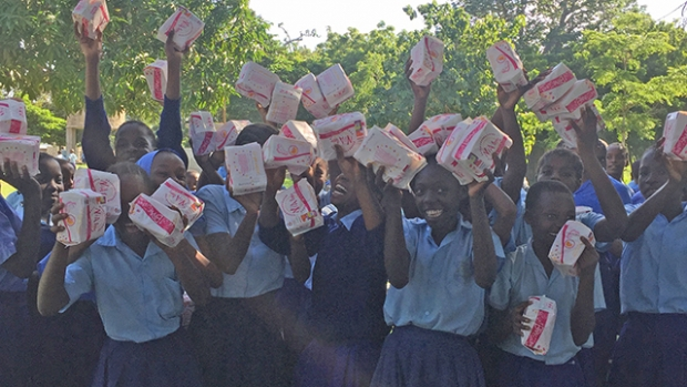 This is a picture of rural youth in Kenya celebrating receiving sexual and reproductive health information and hygiene products.