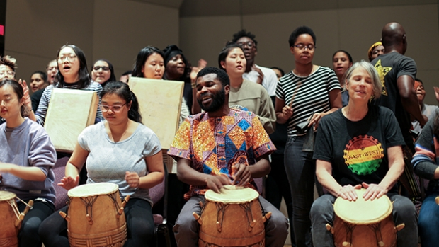 Michael Ofori, center right, and Faith Conant, right, drum with students as part of the final drumming, dancing and singing performance of their classes.