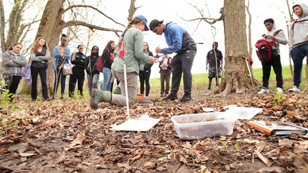 Kate Ballantine , with a group of students examining a soil sample on the Project Stream site.