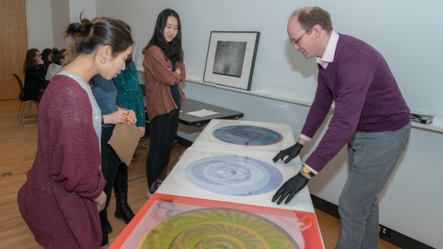 Physics professor Spencer Smith demonstrates for students the interference patterns in works by Albert Gregory.