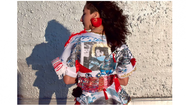This is a picture of a young person in with their back to the viewer, face in profile. They are wearing a colorfully embellished top.