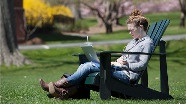 Image of student with laptop on Skinner Green.