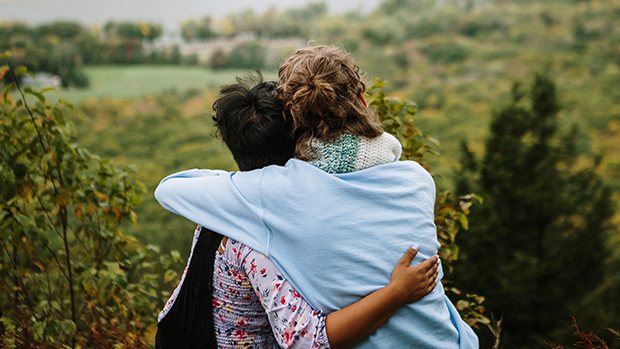 Two students embracing while they look into the distance