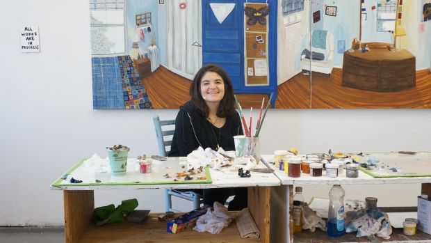 Mount Holyoke graduate Anna Berlin sitting at a desk surrounded by art.