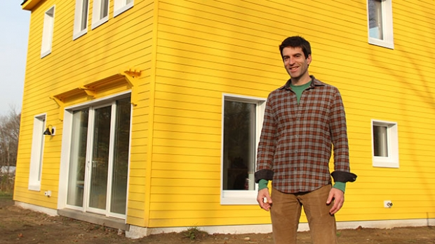 Image of Alexi Arango in front of the Potwine Passive House.