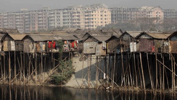 Photo of homes built over the side of a canal with highrises in the background