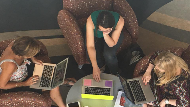 Photo of three graduate students working on laptops.