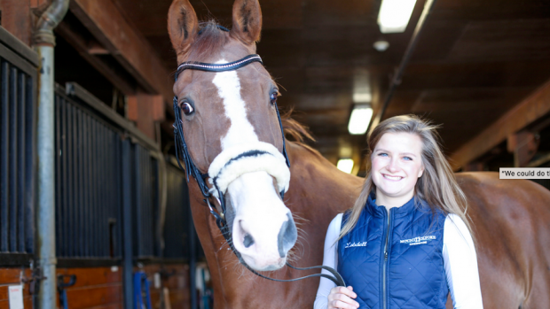 A student stands with a horse in the Equestrian Center barn
