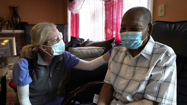 Dr. Megan Young '99, left, offers support to Edouard Joseph, 91, moments after giving him a COVID-19 vaccination. Both are in Joseph's living room and both are masked.