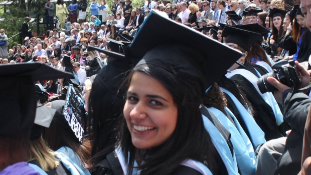 Photo of Areeba Kamal in a graduation cap and gown smiling at the camera.