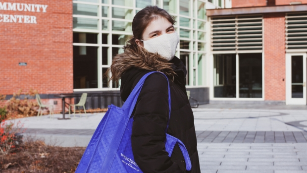 A masked student outside of the Dining Commons, with a reusable lunch tote slung over her shoulder.