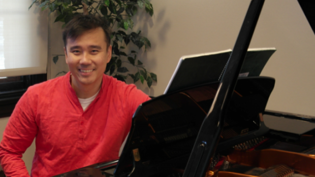 Professor Hui in a red shirts sits at his shiny black piano.