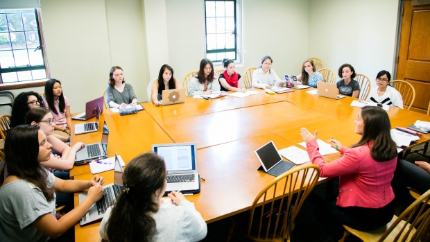 Photo of MHC students seated at tables in a classroom having a discussion