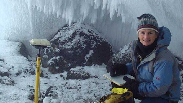 Nelia W. Dunbar '83 sits in an ice cave conducting field work in Antartica.