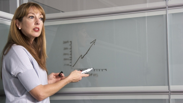 A teacher pointing to a graph on a whiteboard