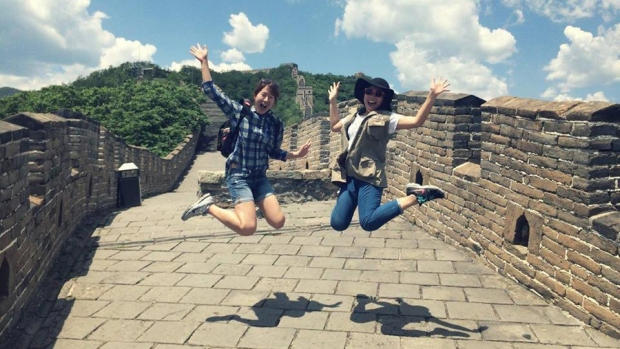 Phuong Nguyen '17 jumping with friend in front of the great wall of China.