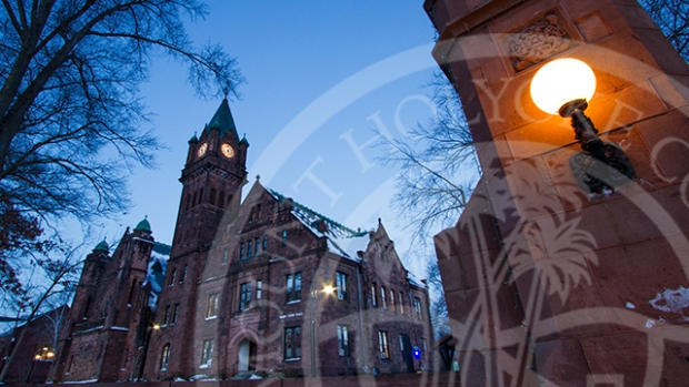 Photo of the Mount Holyoke College gate at dusk with the overlay of the College seal