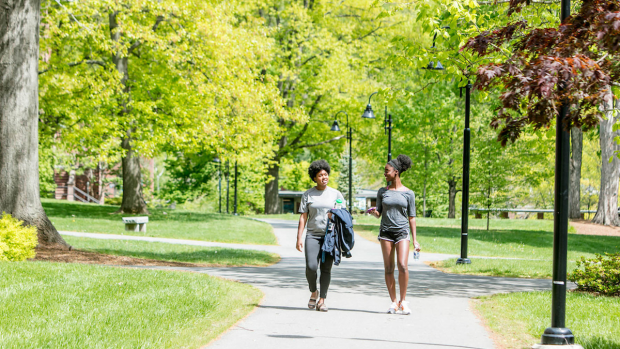 Photo of two students walking on a path through campus