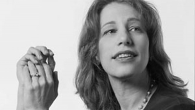 Susan Kare, smiling and looking slightly off camera in black & white