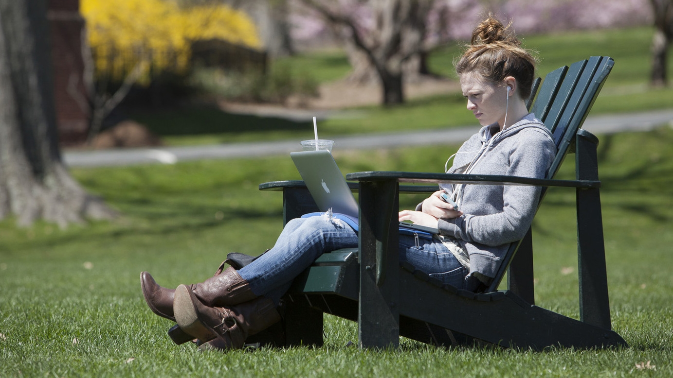 Student working on laptop while sitting in the sun Skinner Green.