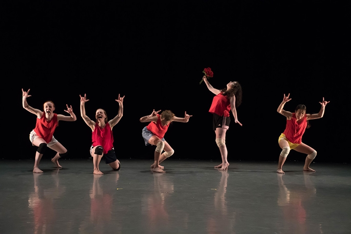 Five dancers, crouching onstage, with arms overhead bent at right angles.