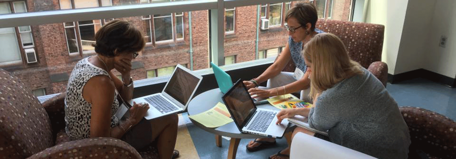 Photo of three graduate students working around a table
