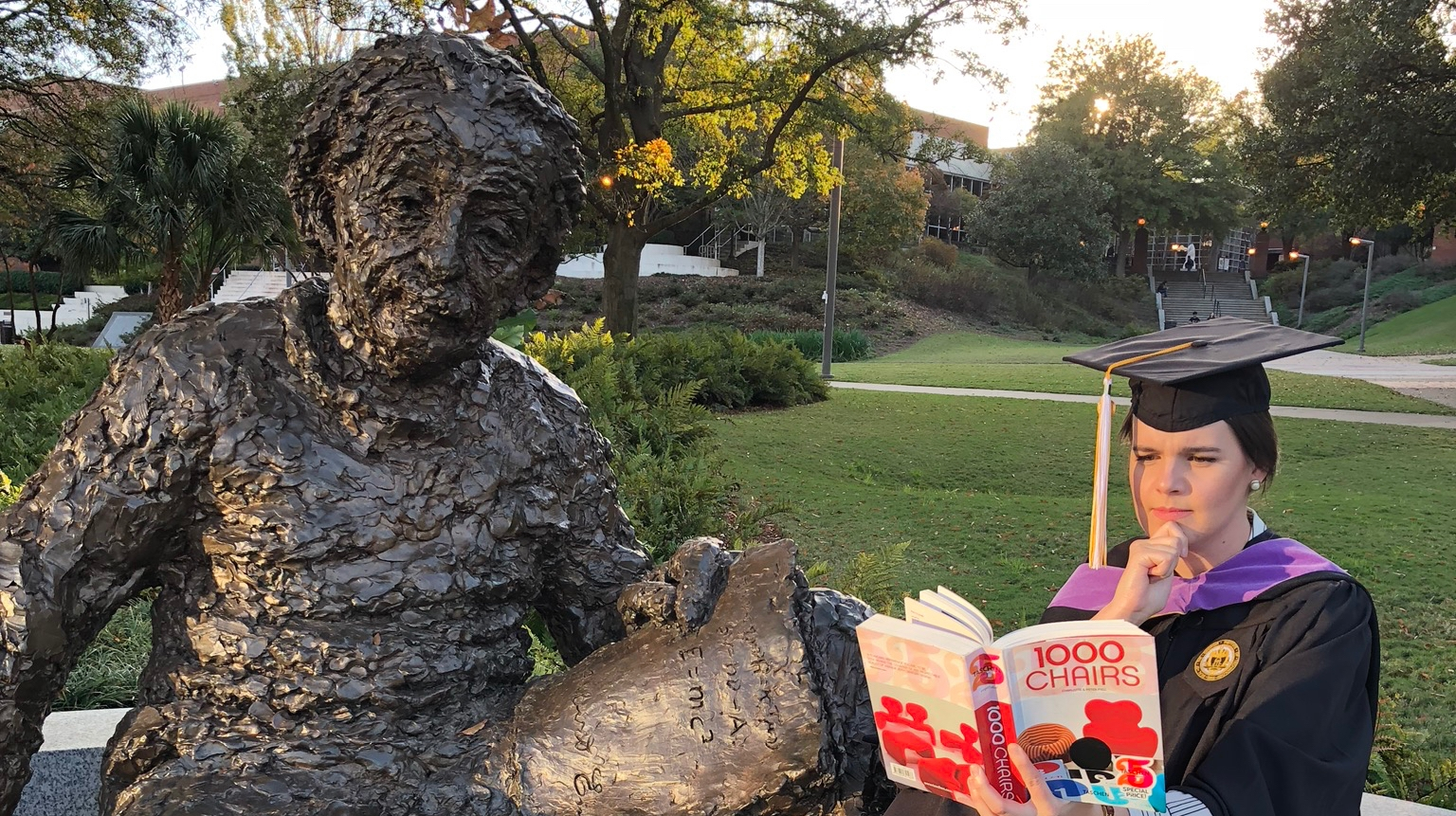 "Mount Holyoke graduate Allie Miller reading ""1000 Chairs"" while sitting next to a statue of Albert Einstein. Miller is dressed in their Masters of Industrial Design graduation regalia."