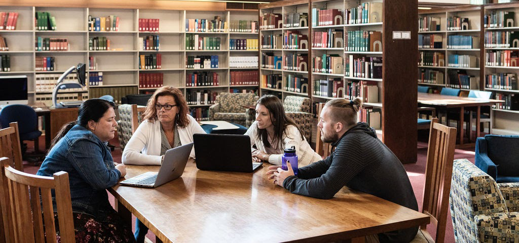 Adult students around a table in Williston library.