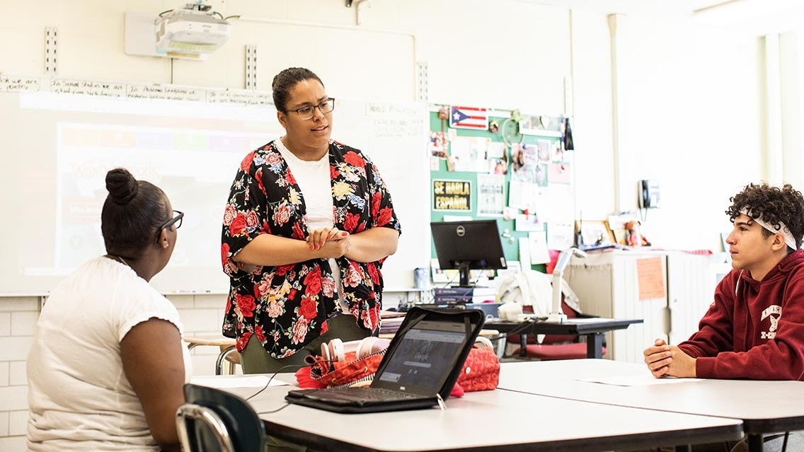 Stephani Lopez Rodriguez teaching two students in a classroom.