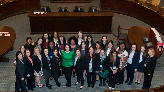 Group photo of students and alums in the Massachusetts Senate chamber
