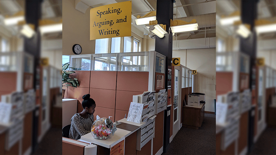 Photo of the SAW Center front desk with a student sitting behind the reception counter.
