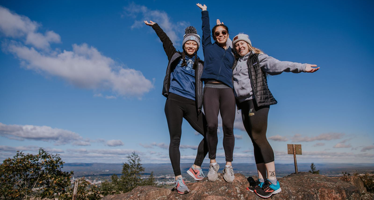 Photo of three Mount Holyoke College students celebrating Mountain Day