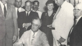 Frances Perkins watches FDR sign the Social Security Act.