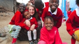 SHOFCO volunteer surrounded by students in Kibera