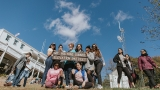 A group of students poses at the summit sign on the top of Mount Holyoke on Mountain Day 2018.